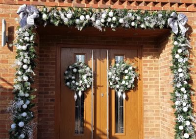 Door surround decorated in snowy whit garland and matching wreat