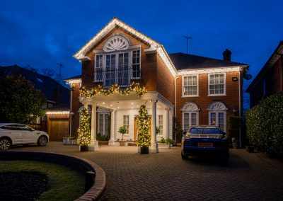 House Exterior lighting, draped Garland and Cone Trees