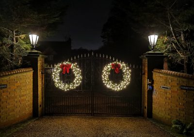 Two 48 inch illuminated wreaths with red bows on this house in B